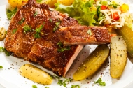 Grilled ribs, baked potatoes and vegetables