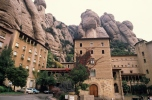 Rocky massif dominating over houses standing in Monserrat, Spain
